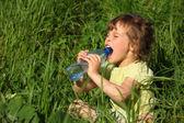 Niña se sienta en la hierba y bebe agua de botella de plástico — Foto de Stock