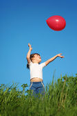 Little girl plays with red balloon in grass — Stock Photo