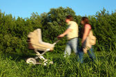 Pair with children's carriage in movement in park — Foto Stock