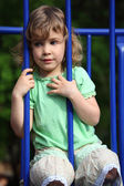 Little girl sits keeping for protection rods — Stock Photo