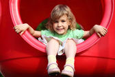 Little girl sits in red plastic hole on playground — Stock Photo