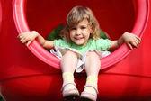 小女孩坐在操场上的红色塑料孔 — 图库照片