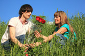 Guy gives to girl bouquet of roses among grass — Stock Photo