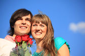 Young pair with bouquet of roses against sky — Stock Photo
