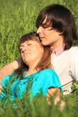 Girl lies on guy sitting in grass — Stock Photo