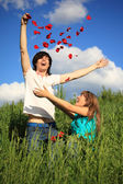 Young pair scatters petals of roses in grass — Stock Photo