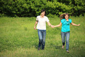 Young pair runs, keeping for hands, on grass in park — Stock Photo