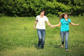 Giovane coppia gira, mantenendo per le mani, sull'erba nel parco — Foto Stock