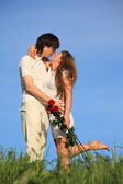 Girl with bouquet of roses kisses guy on grass against sky — Stock Photo