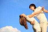 Guy holds girl for waist against sky — Stock Photo