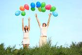 Meisje en jongen staan in gras met veelkleurige ballo — Foto de Stock