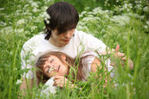 Girl lies in lap of guy sitting in grass — Stock Photo