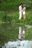 Young pair stands on bank of pond — Stock Photo