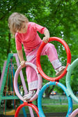 Little girl on pipes on playground — Stock Photo