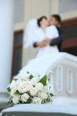 花束和新婚的夫妇接吻 — 图库照片