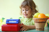 Smiling little girl plays shop — Stock Photo