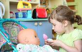 Little girl feeds doll — Stock Photo