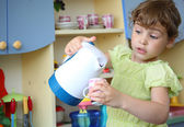 Little girl with kettle and cup in hands — Stock Photo