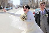 Bride with fiance on street stops car — Stock Photo