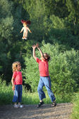 Boy and girl in park toss up upward doll — Stock Photo