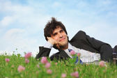 Businessman lies on grass on one side with closed eyes — Stock Photo