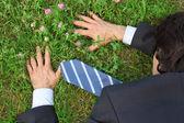Businessman lies prone on grass, top view — Stock Photo