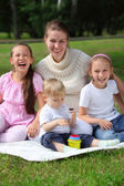Laughing mother and children sits on laying on grass — ストック写真