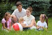 Rodzina pięciu odkryty latem siedzieć na trawie z piłką — Zdjęcie stockowe