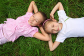 Two girls lie on grass with closed eyes, head to head — Stock Photo
