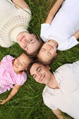 Parents with children lying on grass, view from top, head to hea — Stock Photo