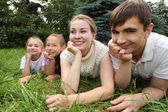 Family of four lying on grass and looks — Stock Photo