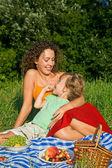 Graziosa ragazza e giovani donne mangia ciliegie picnic — Foto Stock