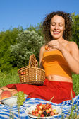 Young Women will get from basket sweet cherries in garden — Stock Photo
