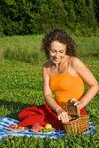 Jonge vrouwen krijgt van mand fruit in tuin — Stockfoto