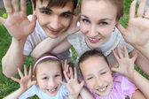 Parents stand with two children outdoor with opened palms, top — Stock Photo