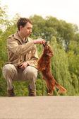 Jonge man speelt met zijn schattig teckel buiten — Stockfoto