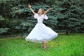 Girl in white dress dances on lawn with lifted hands — Stock Photo