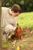 Young man and his adorable dachshund outdoor looks on each othe — Stock Photo