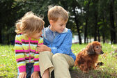 Children with dachshund sit on grass — Stock Photo