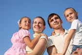 Två föräldrar håller barn på händer mot himlen — Stockfoto