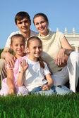 Rodzina czterech odkryty latem siedzi na trawie — Zdjęcie stockowe