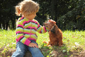 Little girl caress dachshund outdoor — Stock Photo