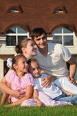 Family from four sits on grass against house — Stock Photo