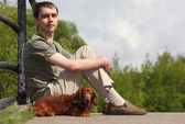 Young man and his dachshund sits outdoor in summer — Stock Photo