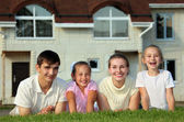 Family from four lies on grass against house — Stock Photo