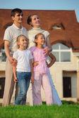Famille de quatre tribunes sur herbe contre maison — Photo
