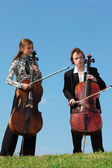 Two musicians play violoncellos against sky — Stock Photo