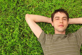 Teenager lies on grass — Stock Photo