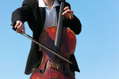 Close-up musician plays violoncello against sky — Stock Photo