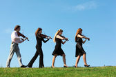 Four musicians go and playing violins against sky — Stock Photo